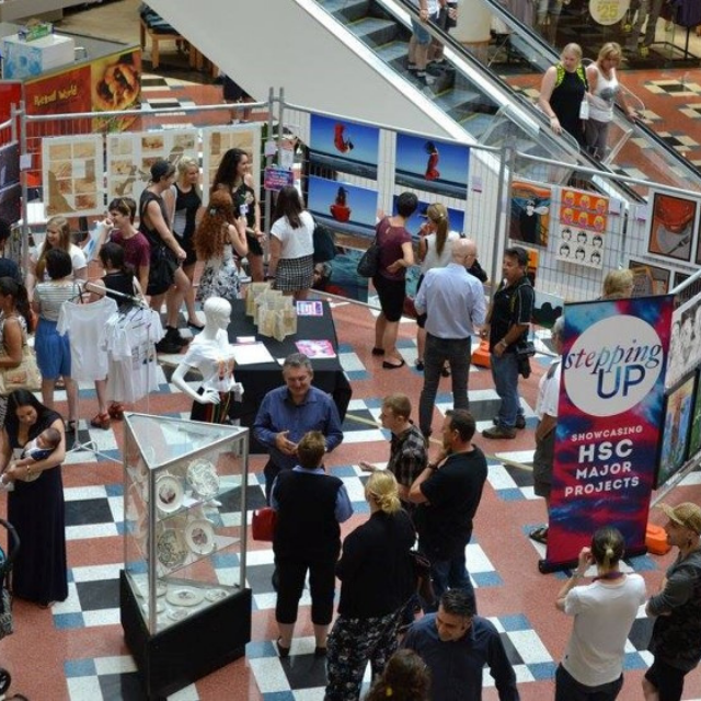 A HSC art exhibition in the middle of a shopping centre. It is opening night and people are mingling with young artists and the organisers.