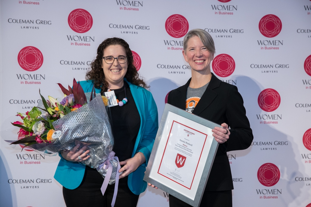 Natalie accepts the Young Women of the West Award from Dianne McGrath. They are both beaming with big smiles.